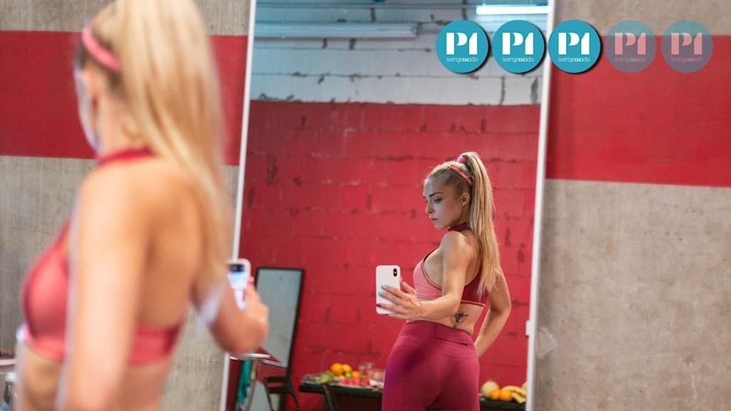 """En ung kvinna står med ryggen en mot en spegel och tar en bild med sin mobil. Scen från filmen """"Sweat""""."""