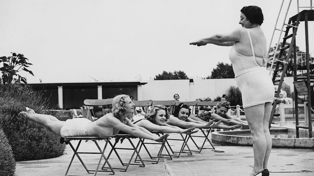 En simlärare visar torrsim för ett antal damer som ligger på mage på en pall och sprattlar med armar och ben
