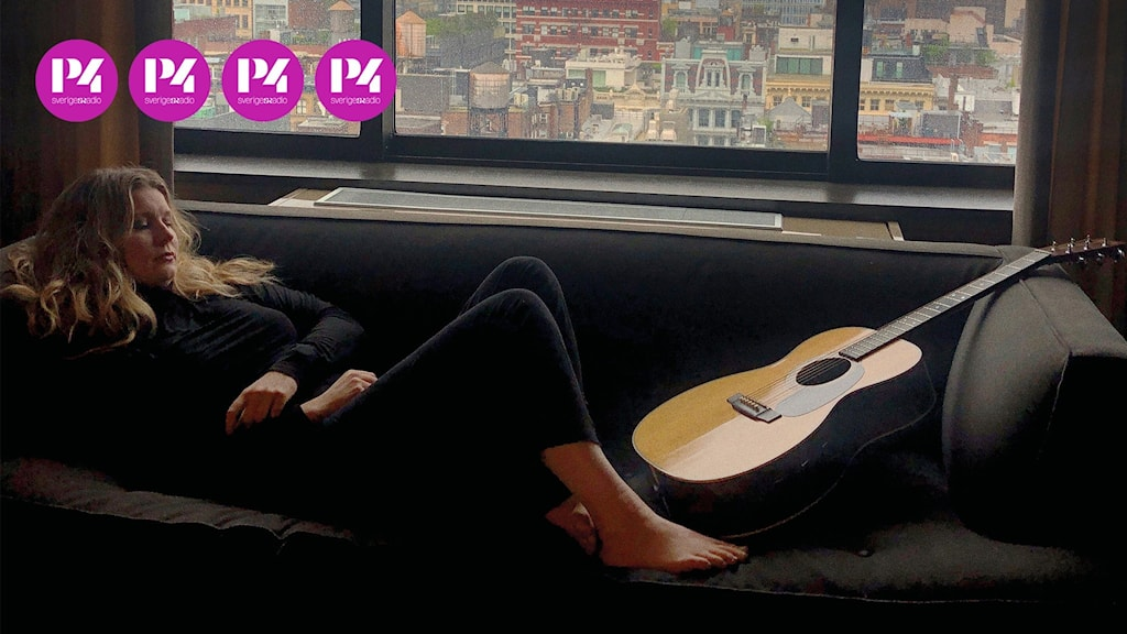 En kvinna ligger på en soffa med en gitarr intill.