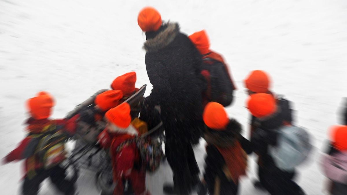 En förskolepedagog tillsammans med en massa barn.