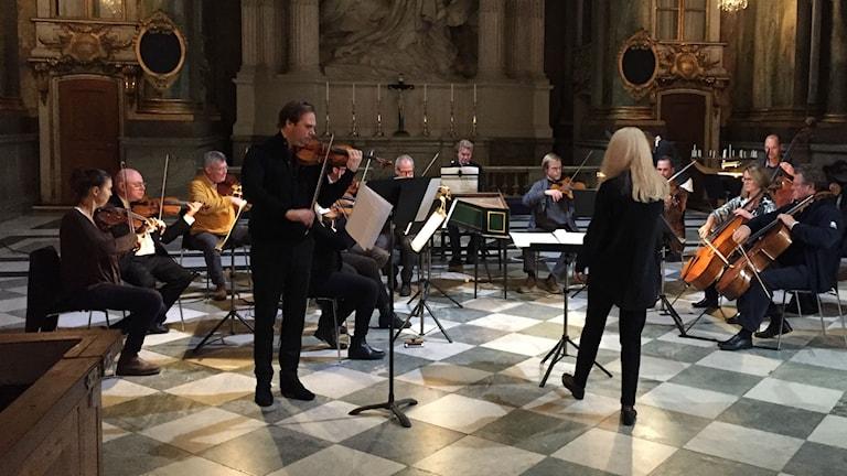 Idégivaren och violinisten Christian Svarfvar, Stockholms solister och dirigenten Maria Eklund repeterar i Slottskyrkan.