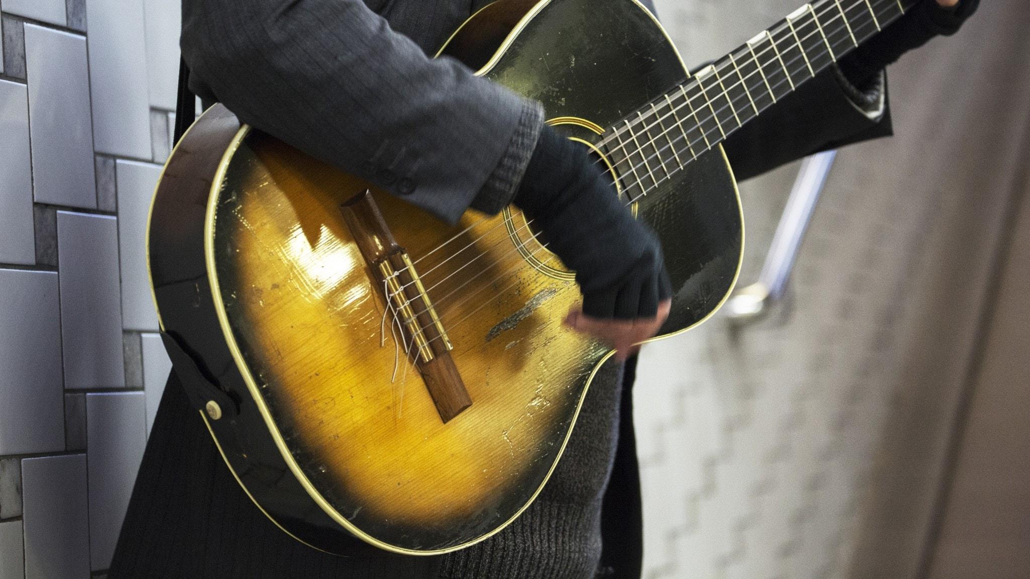 En närbild på en person som spelar gitarr.