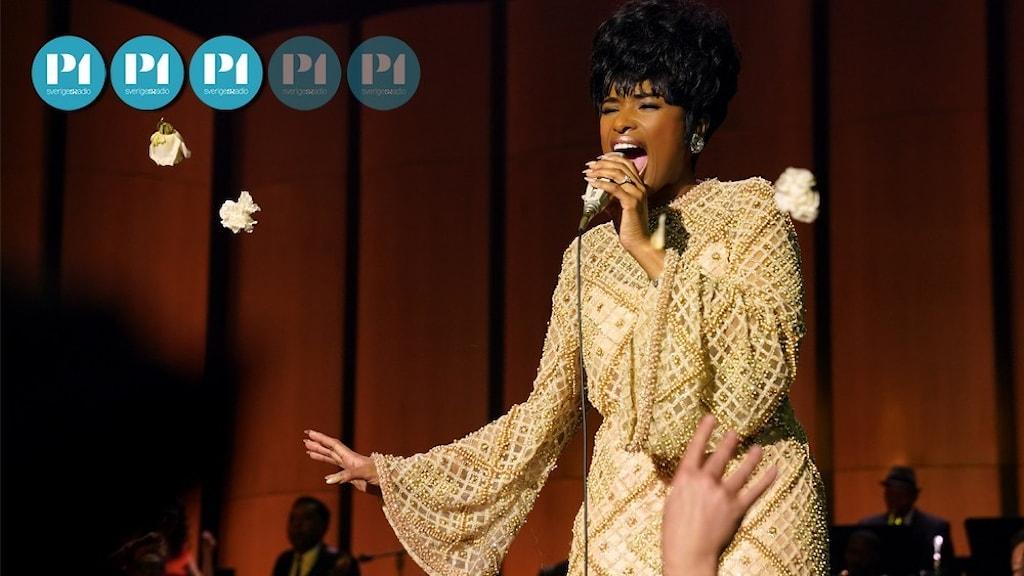En kvinna i guldfärgad palettklänning sjunger inlevelsefullt i en mikrofon.