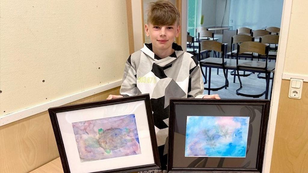 12-åriga Rasmus Ericzzon håller upp två av sina tavlor.