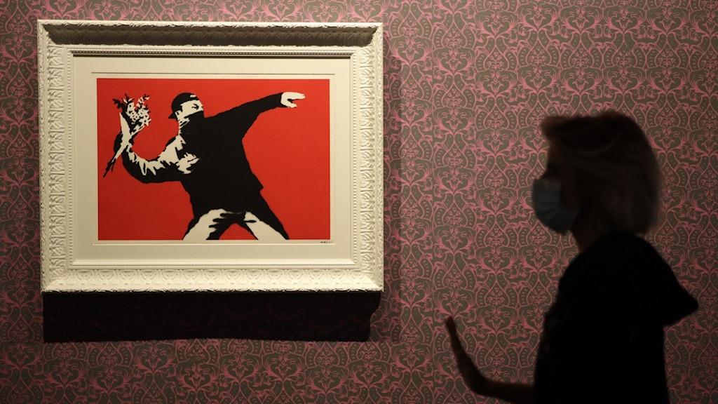 """En tavla föreställande Banksys """"Flower Bomber"""", en maskerad man som kastar en blombukett."""