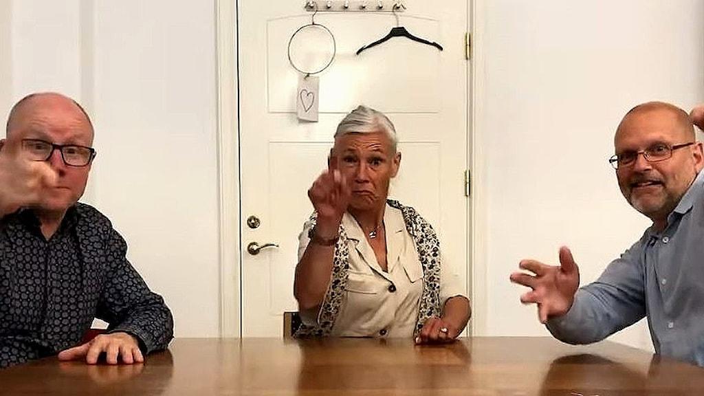 Tre liberala politiker sitter vid ett bord och kollar in i kameran.