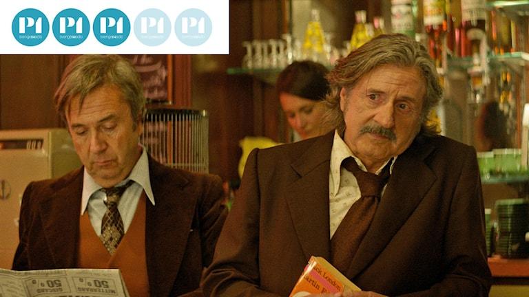 En bild av två franska män på café, klädda i bruna 70-talskostymer.
