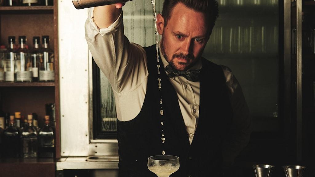 Oscar stenström, bartendern, häller upp en drink och stirrar på den.