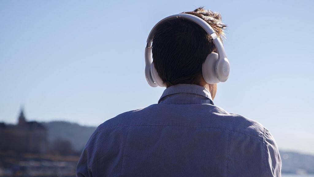Bild av en man fotograferad bakifrån. Han står och tittar ut över öppet vatten med ett par stora hörlurar på huvudet.