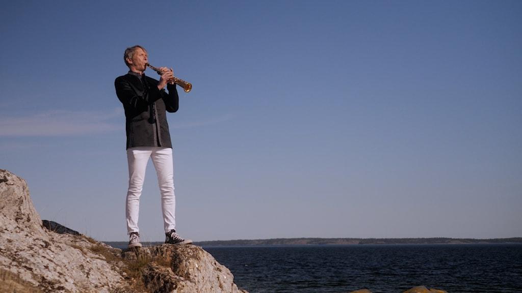 Saxofonisten Anders Paulsson klädd i ljusa byxor och mörk tröja står på en klippa vid havet och spelar sopransaxofon.