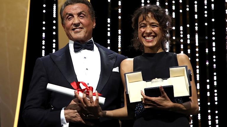 Regissören Mati Diop tar emot sitt pris i Cannes från utdelaren Sylvester Stallone.