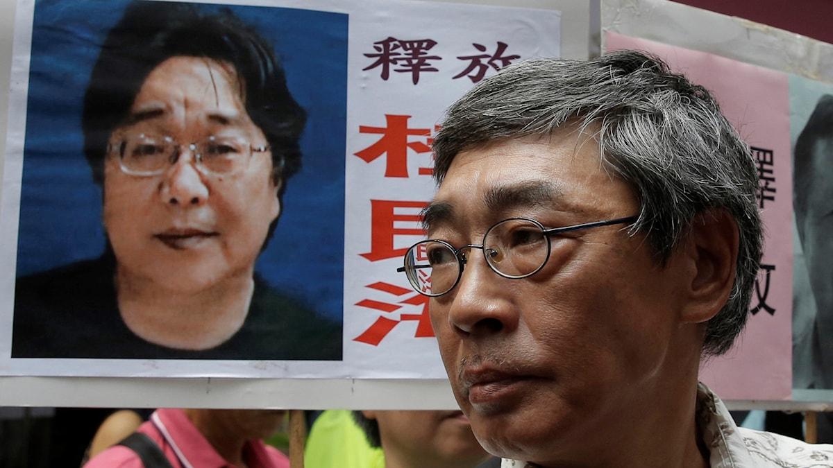 Bokhandlaren Lam Wing-kee vid en skylt med bild på Gui Minhai.
