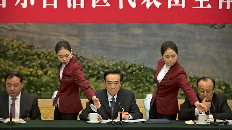 Chen Quanguo, partisekreterare i Xinjiang (mitten) får påfyllning av té under en partikongress i Peking i mars 2019.