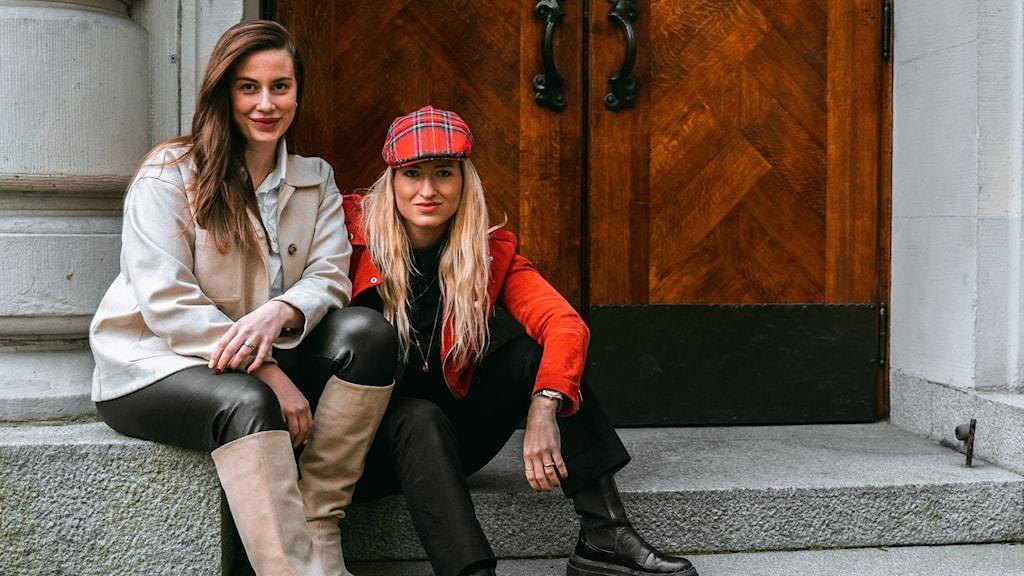 Två kvinnor sitter utanför en träport.