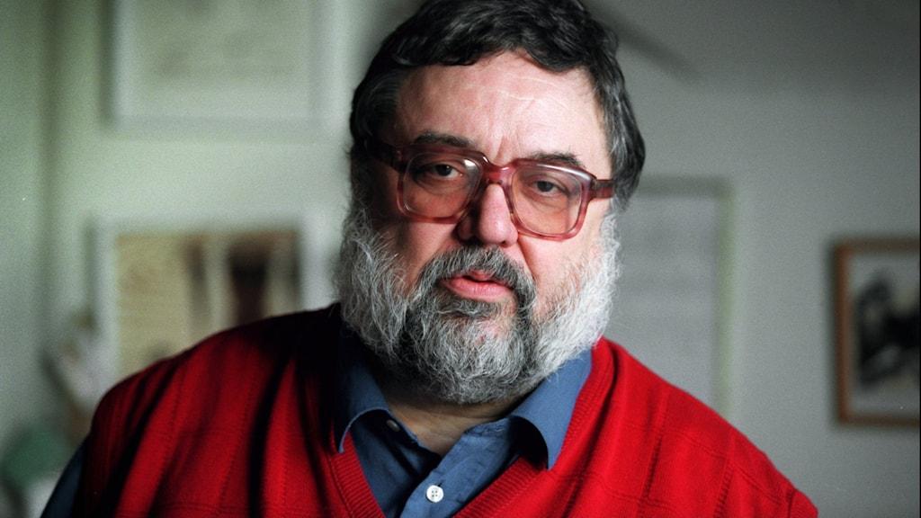 Journalisten och författaren Staffan Skott klädd i röd kofta och blå skjorta.