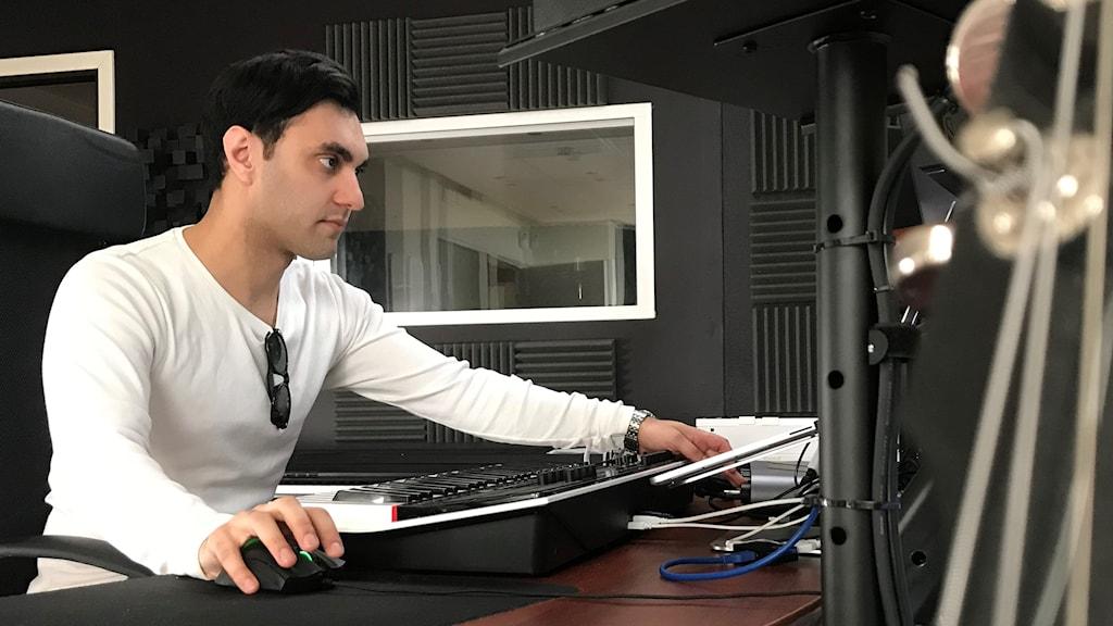 Mani Ajami sitter på sin producentplats.
