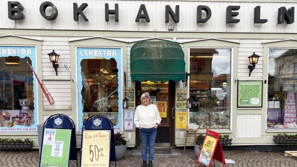 Kerstin Åkerlund, klädd i vit kofta, står utanför sin bokhandel i Trosa.