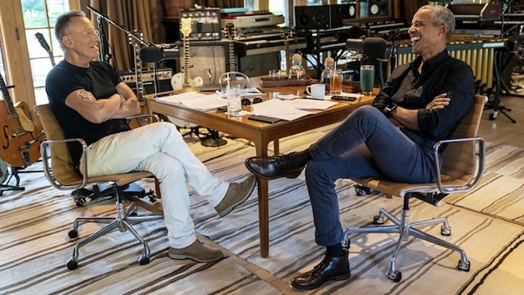 Bruce Springsteen och Barack Obama sitter tillsammans vid ett bord och skrattar.
