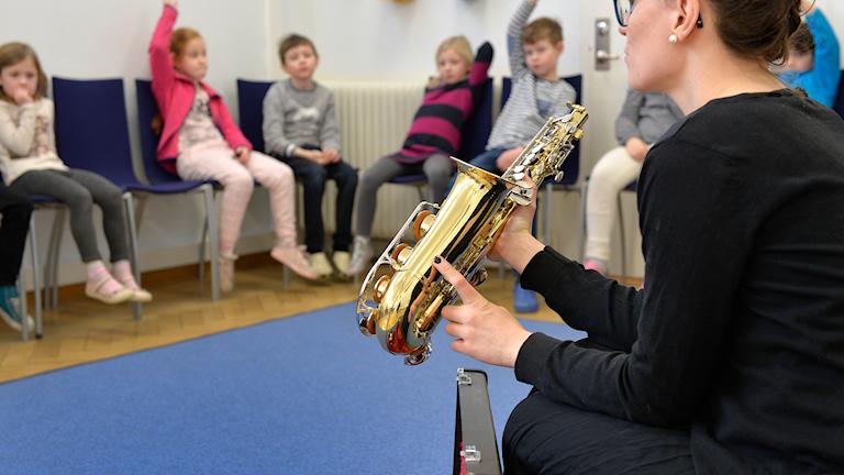 En lärare visar blåsinstrument för elever i första klass på grundskolan under en lektion i musik.