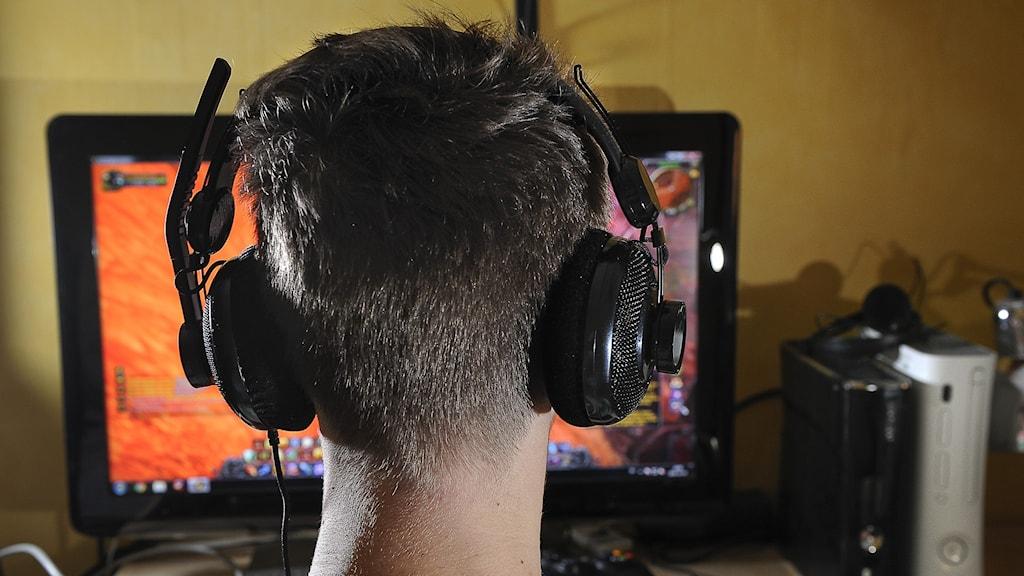 person med hörlurar framför datorskärm