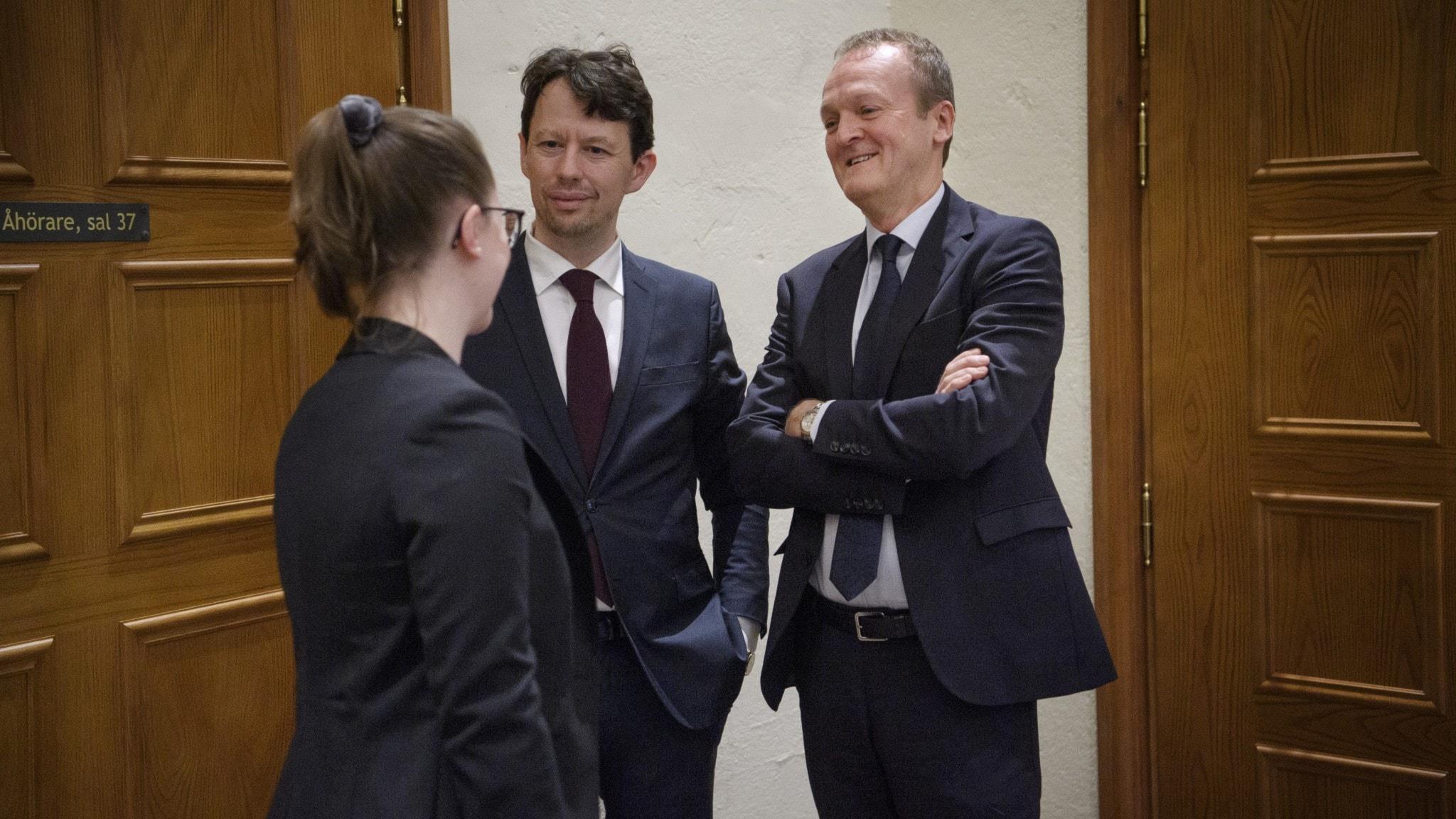 Tre jurister utanför en rättssal.