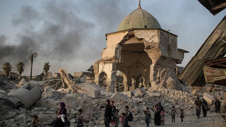 Flyende civila passerar den berömda al-Nurimoskén i Mosul.