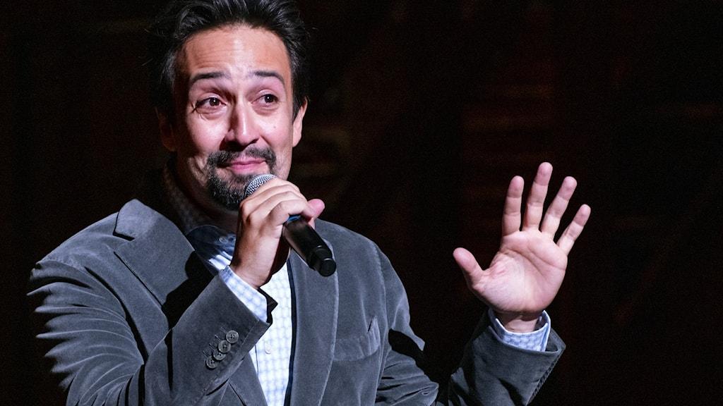 Lin-Manuel Miranda talar i en mikrofon på scen.