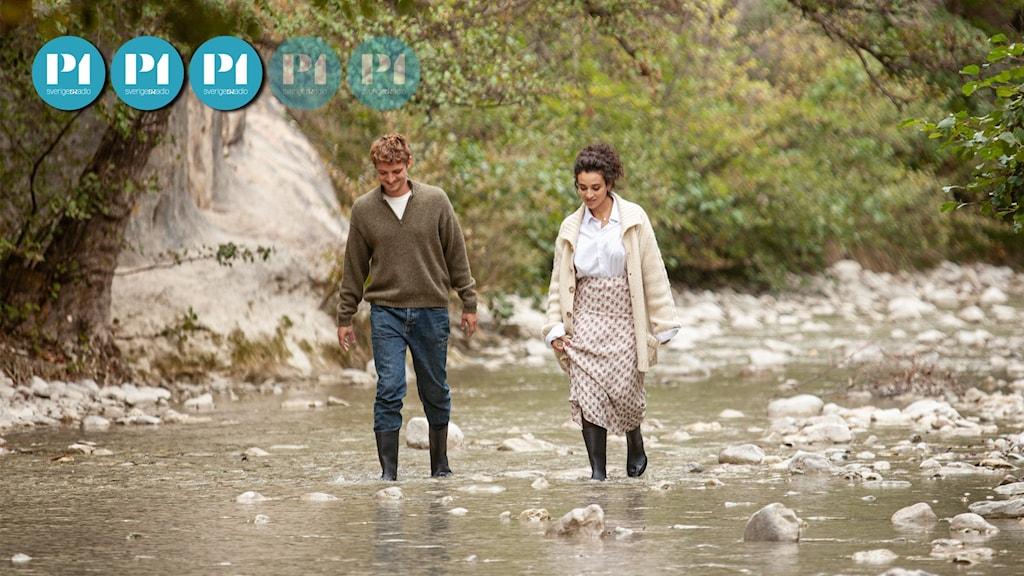 """Stillbild från filmen """"Saker vi säger, saker vi gör"""". Ett par går hand i hand i en grund bäck."""