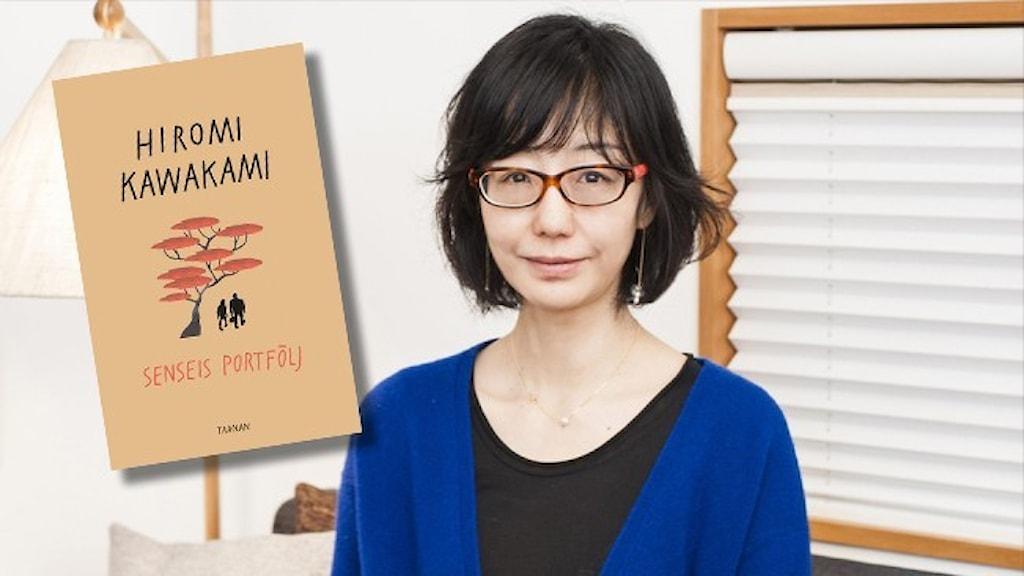 Författaren Hiromi Kawakami klädd i blå kofta och svart t-shirt i ett rum med vita väggar och en vit lampskärm.