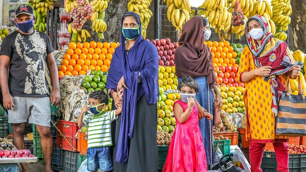 Man, barn och kvinnor vid fruktstånd i Kerala, Indien.
