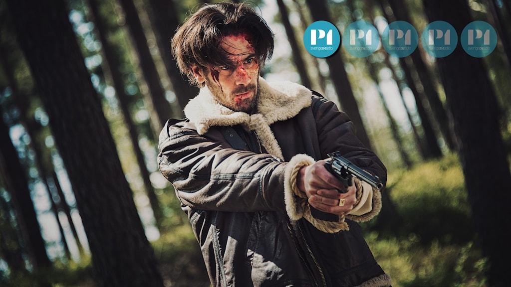 """Skådespelaren Ola Rapace i filmen """"Vitt skräp"""". Han står i en fodrad läderjacka med en pistol riktad neråt, blodig i ansiktet och med rep runt handlederna."""