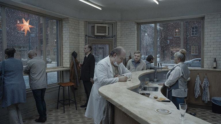 """Tandläkaren tar ett glas i baren i filmen """"Om det oändliga""""."""