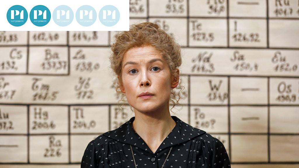 En bild på Marie Curie med hår uppsatt i knut framför en bild av periodiska systemet.