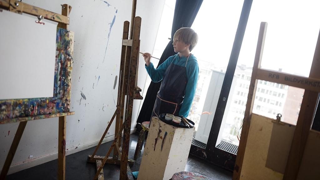 En pojke målar med olja på en duk.