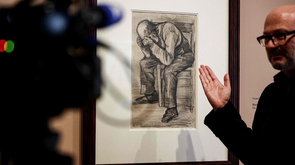 En man gestikulerar mot en tavla på väggen.