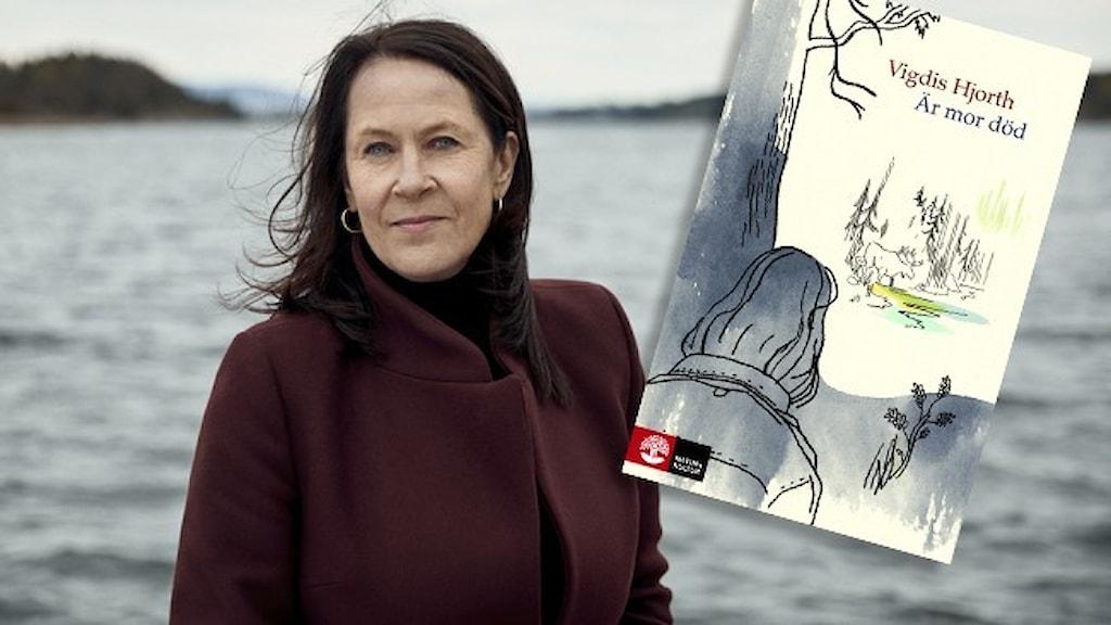 Porträtt av författaren Vigdis Hjort, klädd i vinröd kappa, stående vid ett öppet vatten. Infälld i bilden är omslaget till hennes bok Är mor död.