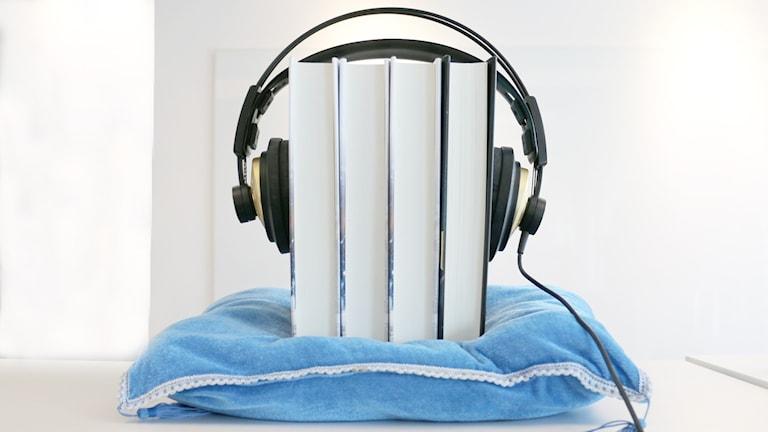 Ett par böcker på en kudde med ett par hörlurar över bokryggarna för att illustrera ljudbok och ljudbokslyssning.