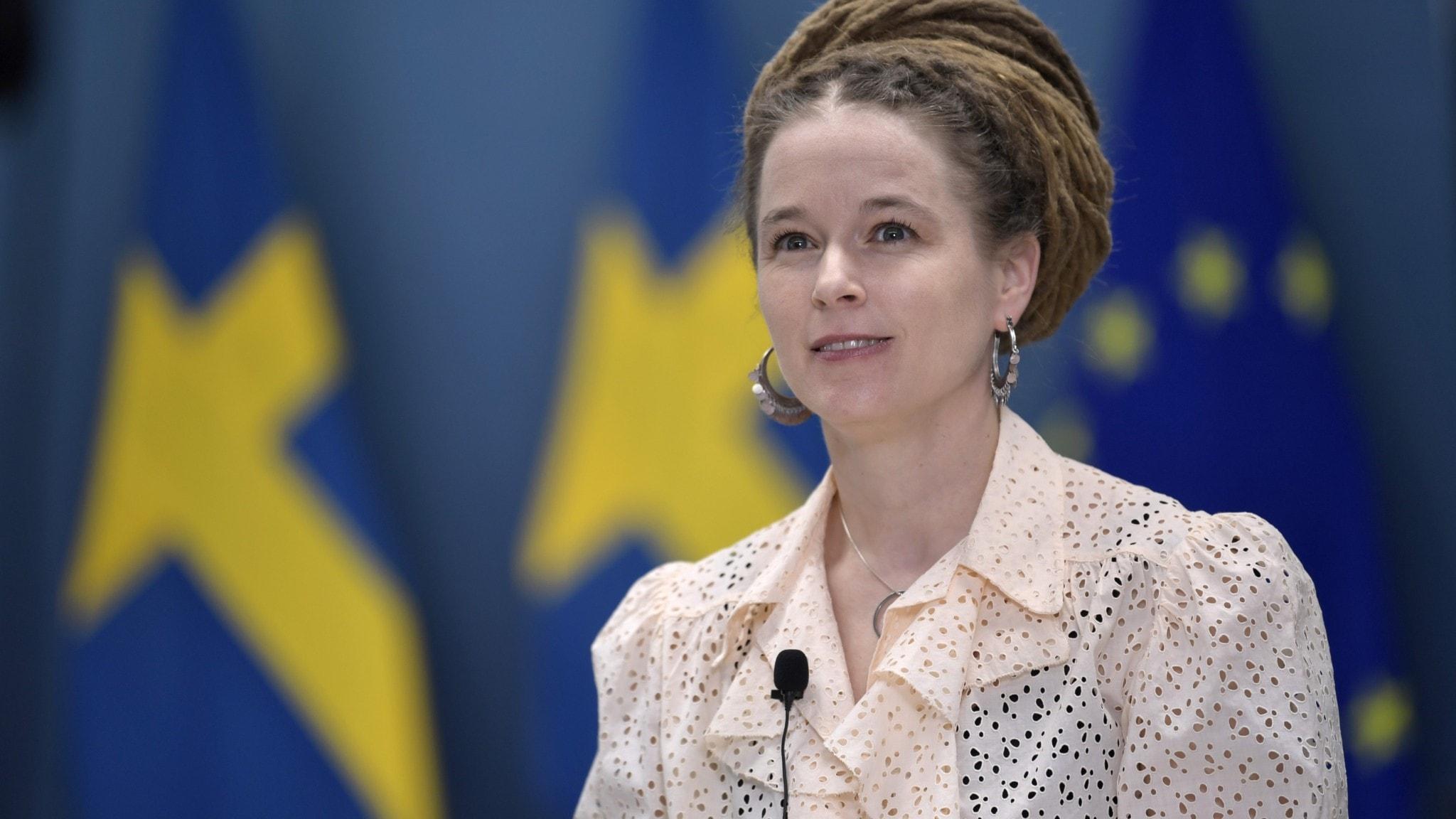 Porträtt av kulturminister Amanda Lind (MP) klädd i ljusrosa blus framför två svenska flaggor och en EU-flagga.