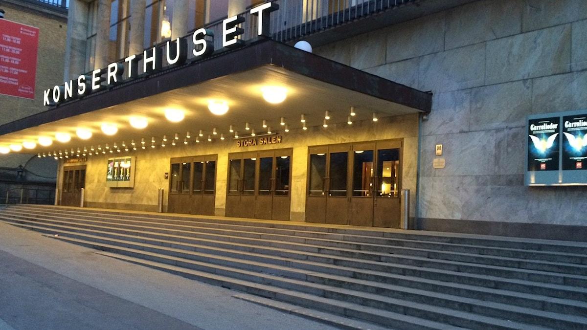 Trappan vid Göteborgs konserthus på Götaplatsen. Kvällsljus. Entrén är upplyst av lampor och neonbokstäver lyser KONSERTHUSET på entrétaket.