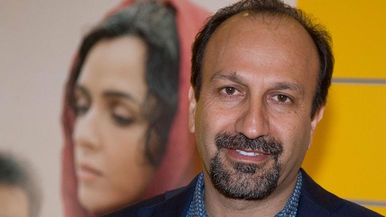 Asghar Farhadi poserar framför en filmaffisch