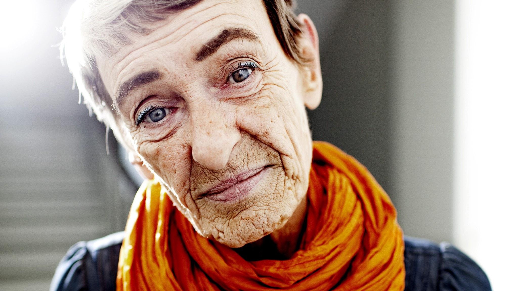 Närbild av Gunilla Bergström, orange skarf runt halsen.