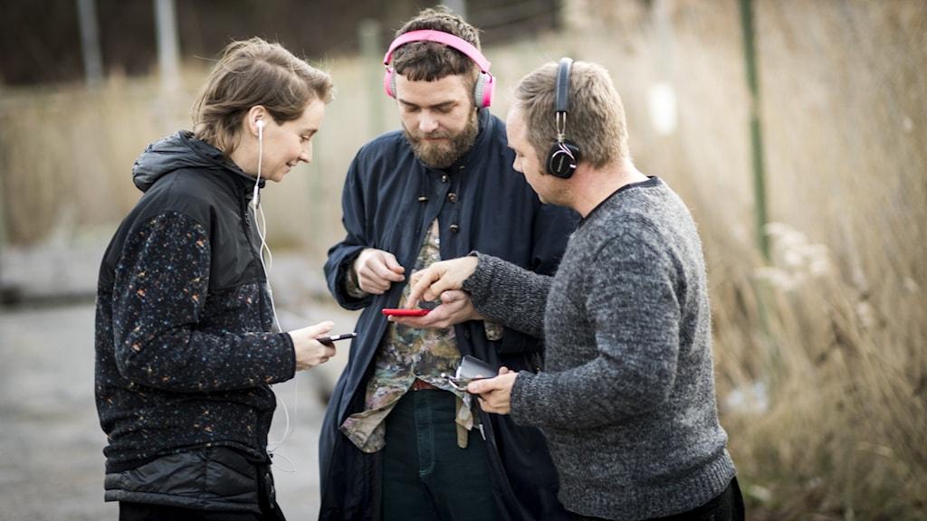 Lisa Färnström, Hampus Norén, Joakim Rindå står med hörlurar och tittar på sina telefoner.