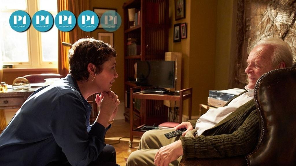 En medelålders kvinna sitter framåtlutad och pratar med en äldre man i en fåtölj.