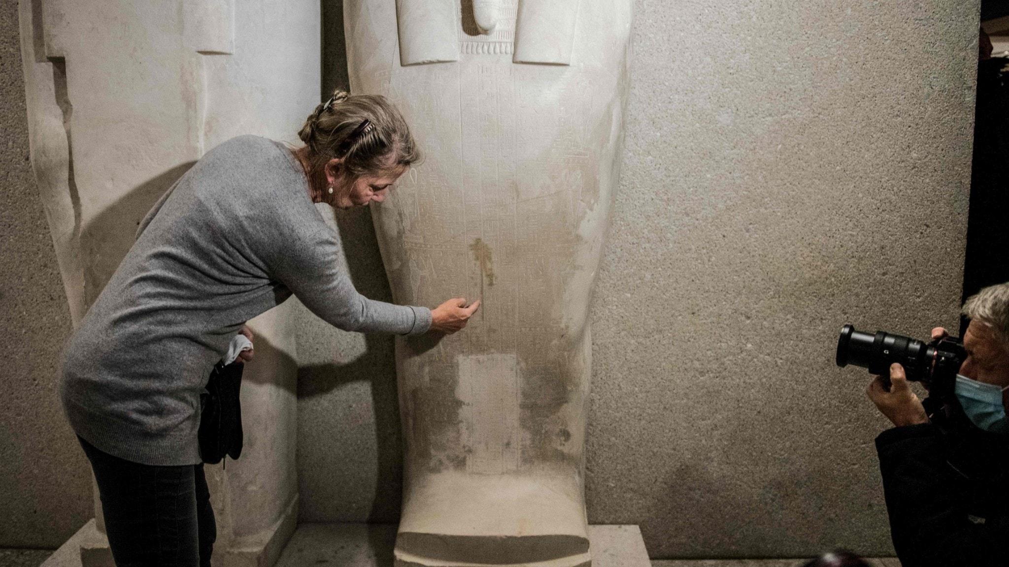 Kvinna pekar ut skador orsakade av en oljig vätska på en stensarkofag.