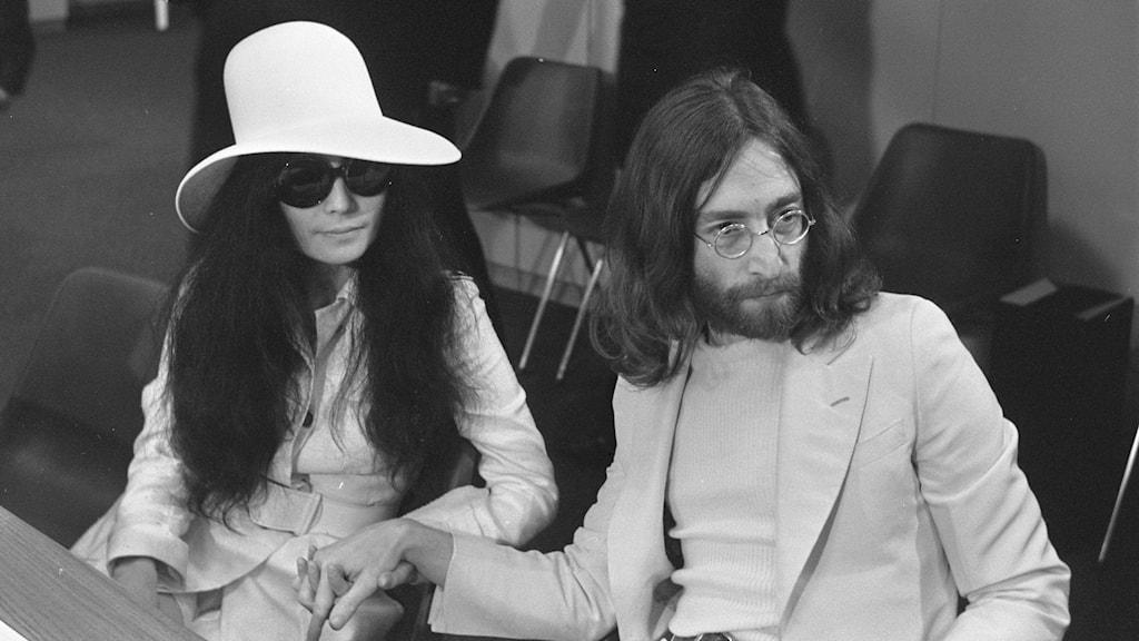 Svartvitt bild av Yoko Ono, klädd i vit hatt och solglasögon, och John Lennon med runda klasögon och ljus kavaj. De håller varandras händer.