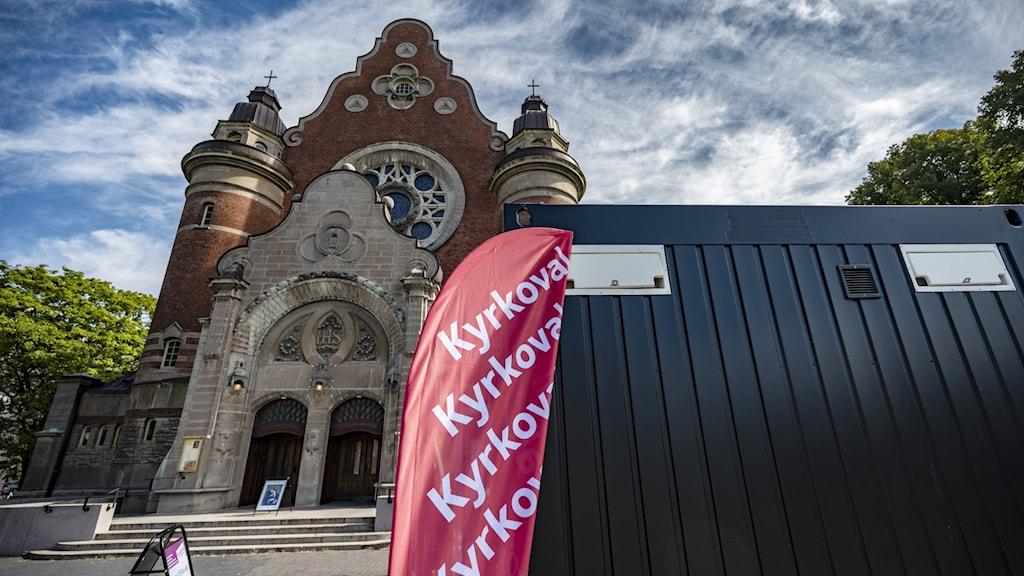 En kyrka i bakgrunden och en vimpel som uppmaningar till röstning i kyrkovalet i förgrunden.