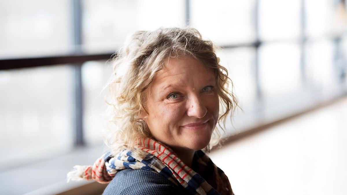 Anna Takanen har en scarf på sig och står framför ett fönster.