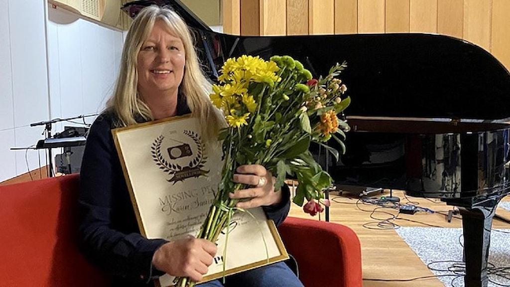 Författaren Karin Smirnoff, mottagare av Sveriges radios novellpris, med blommor och diplom.