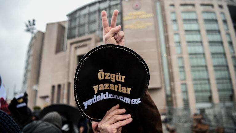 """Protester utanför domstolen i Turkiet inför rättegången mot författaren Asli Erdogan. """"Författares frihet är inte garanterad"""" står det på skylten."""