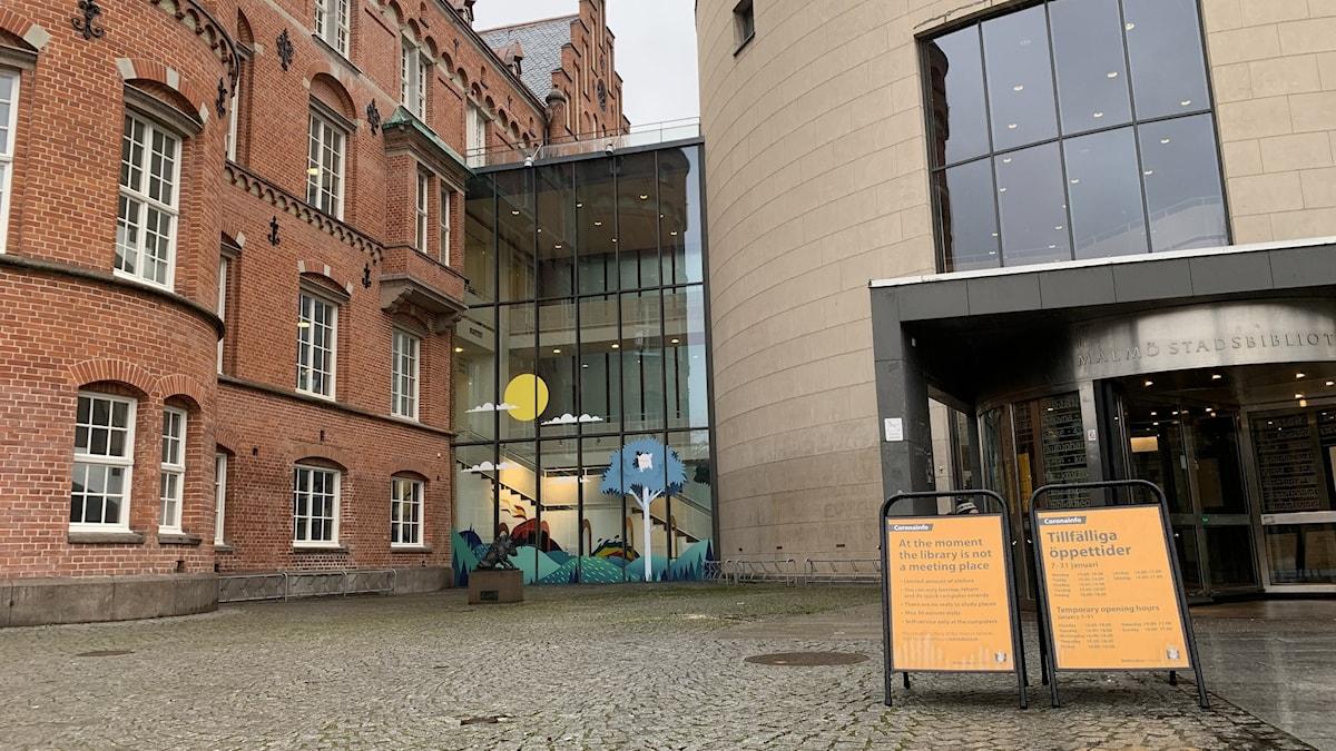 Två skyltar informerar besökare om de särskilda restriktionerna utanför Malmö stadsbibliotek